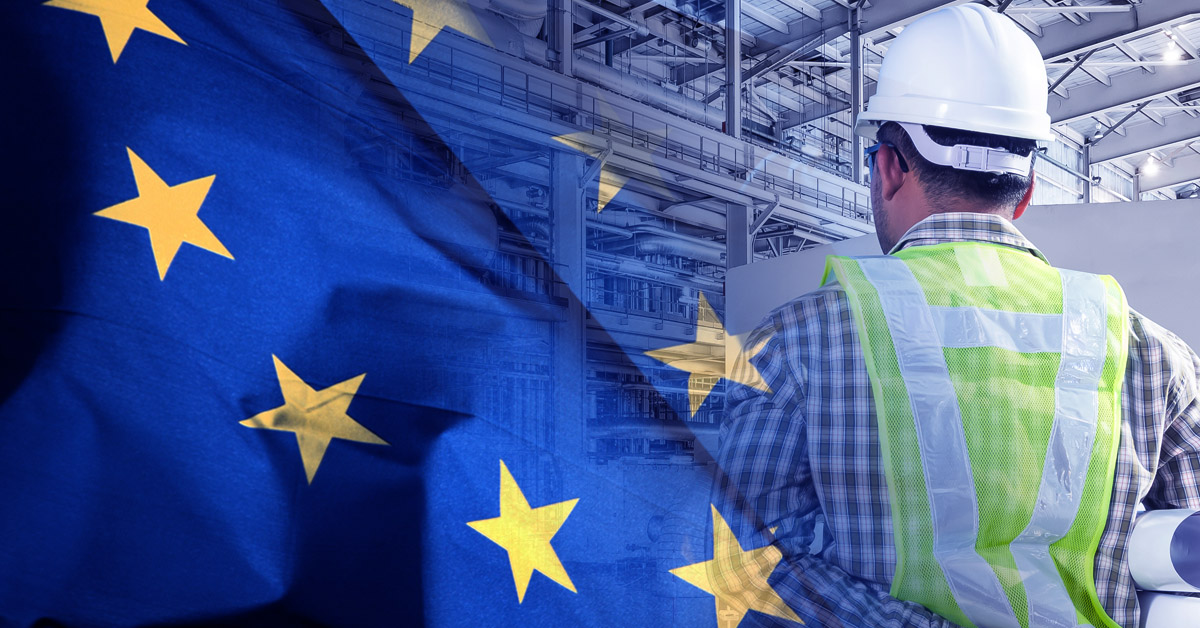 Double exposure of the EU flag and a man wearing a hard hat and hi-viz vest standing in a chemical warehouse