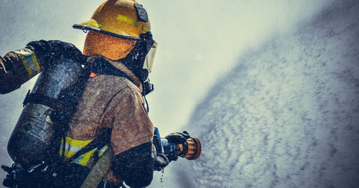 Fireman training to fight fire while wearing personal protective equipment