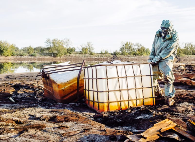 Man in a hazmat suit standing in a muddy area of land lifting a plastic container that is housing chemicals