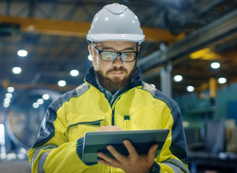 Occupational Safety Manager wearing a hi viz vest and hard hat while assessing information on a digital device.