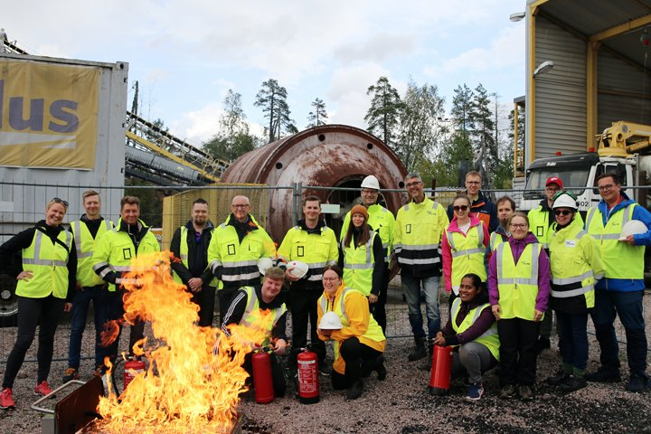 A group of health and safety professionals standing wearing hi-viz jackets, carrying fire extinguishers, to demonstrate fire safety.