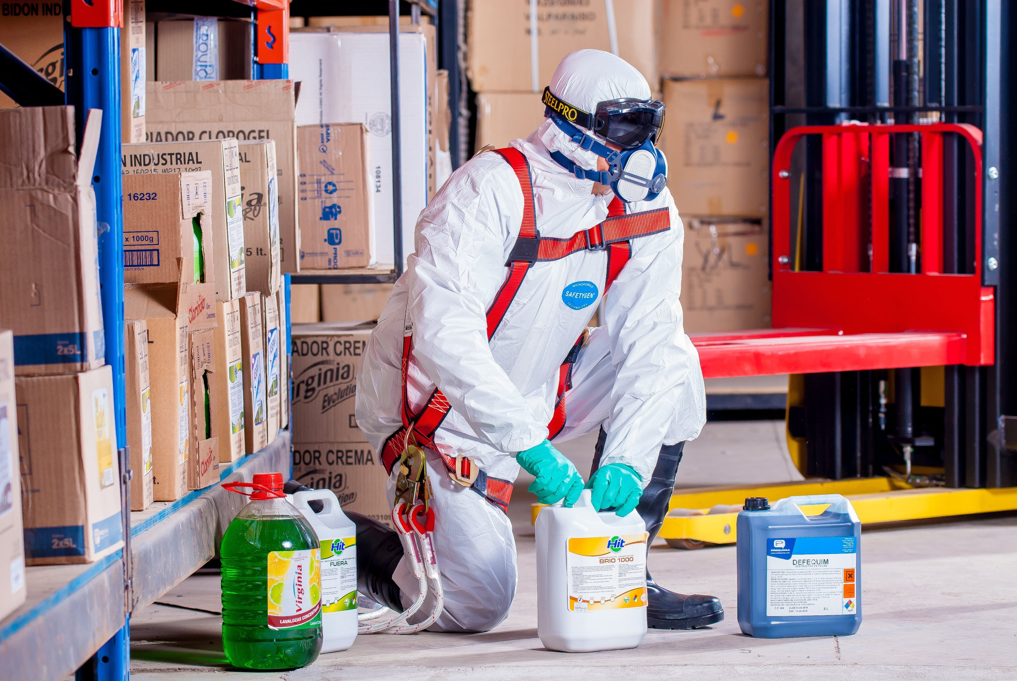 Person kneeling on the ground in a hazmat suit and PPE opening a chemical bottle