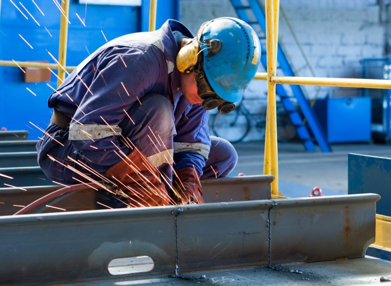 A welder wearing personal protective equipment (PPE) while welding a large piece of metal at work