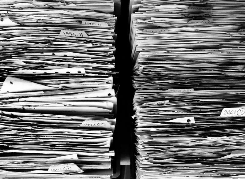 A close up stack of safety data sheets requiring manual processing
