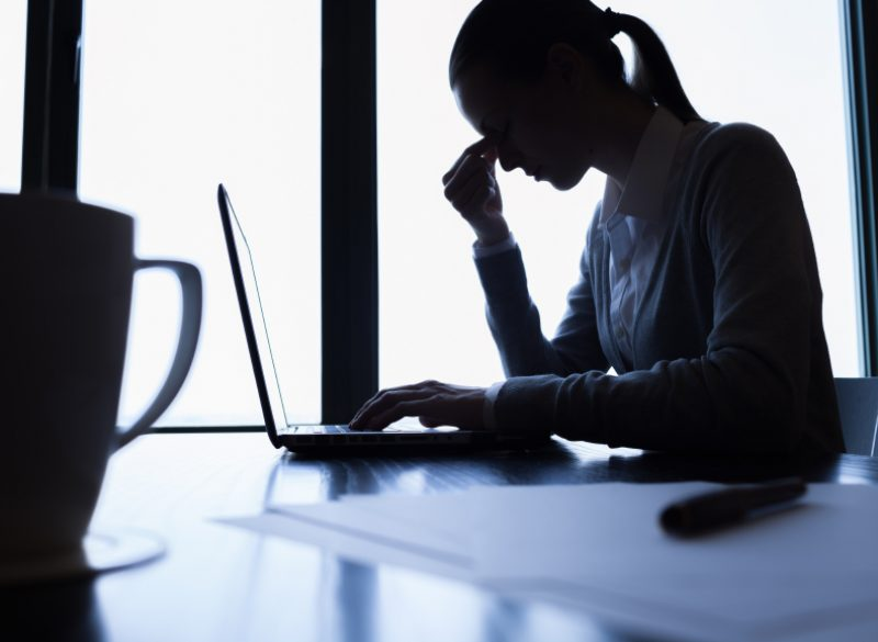 A woman sitting at a table in silhouette with her head in her hand and a laptop in front of her.