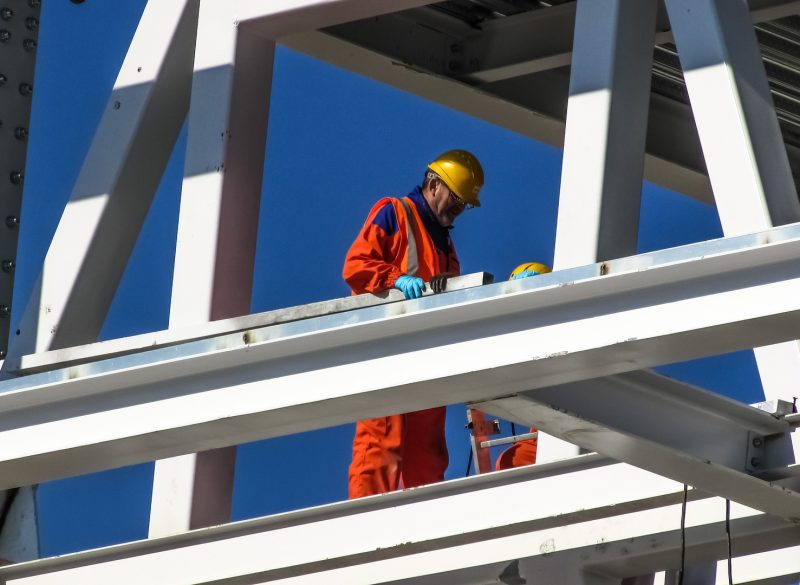 Construction worker wearing proper PPE equipment while working at height on a metal framed structure